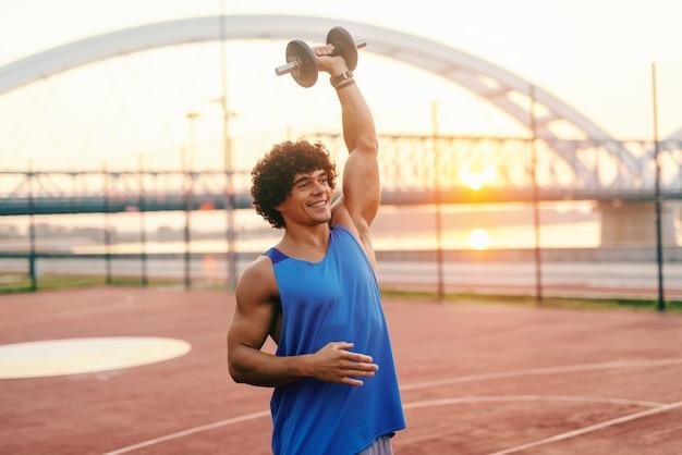 Kaukasischer mann mit zahnigem lächeln und lockigem haar, gekleidet in sportbekleidung, die hanteln hebt, während er am morgen auf dem platz steht.