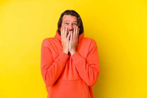 Kaukasischer mann mittleren alters auf gelb schockiert, mund mit händen bedeckend, darauf bedacht, etwas neues zu entdecken.