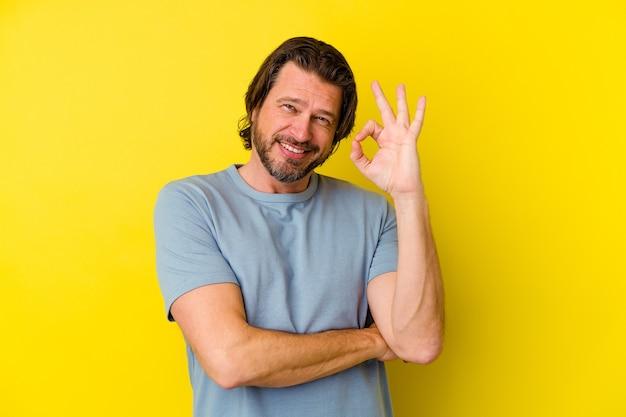 Kaukasischer mann mittleren alters, der auf gelbem hintergrund isoliert ist, zwinkert ein auge und hält eine gute geste mit der hand.
