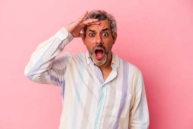 Kaukasischer mann mittleren alters, der auf rosafarbenem hintergrund isoliert ist, schreit laut, hält die augen geöffnet und die hände angespannt.