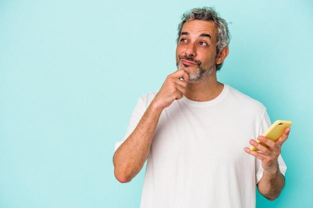 Kaukasischer mann mittleren alters, der ein mobiltelefon isoliert auf blauem hintergrund hält und seitlich mit zweifelhaftem und skeptischem ausdruck schaut.