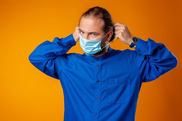 Kaukasischer mann mittleren alters, der medizinische gesichtsmaske gegen gelb trägt