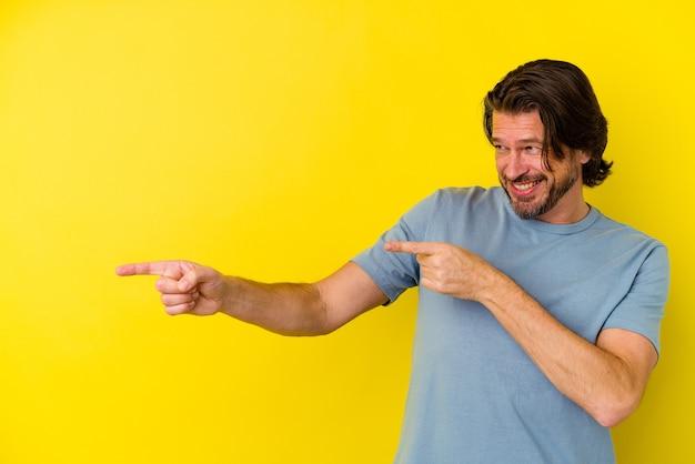 Kaukasischer mann mittleren alters einzeln auf gelbem hintergrund, der mit den zeigefingern auf einen kopienraum zeigt und aufregung und verlangen ausdrückt.