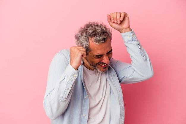 Kaukasischer mann mittleren alters einzeln auf rosafarbenem hintergrund, der einen besonderen tag feiert, springt und hebt die arme mit energie.
