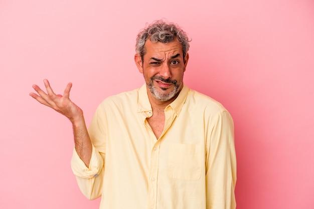 Kaukasischer mann mittleren alters einzeln auf rosafarbenem hintergrund, der in fragender geste zweifelt und die schultern zuckt.