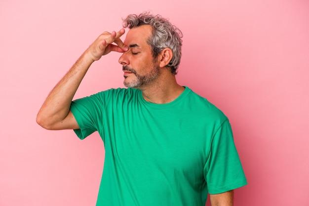 Kaukasischer mann mittleren alters einzeln auf rosafarbenem hintergrund mit kopfschmerzen, der die vorderseite des gesichts berührt.