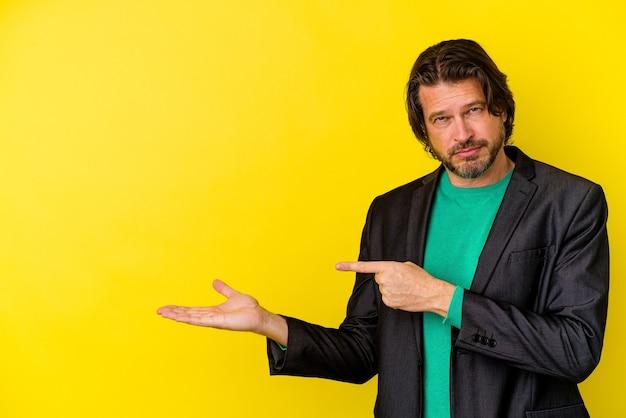 Kaukasischer mann mittleren alters isoliert auf gelbem hintergrund aufgeregt, einen kopienraum auf der handfläche zu halten.