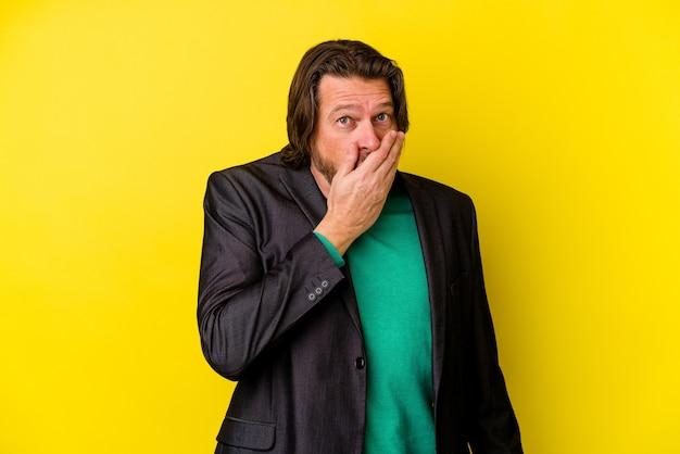Kaukasischer mann mittleren alters isoliert auf gelbem hintergrund, der den mund mit den händen bedeckt, die besorgt aussehen.