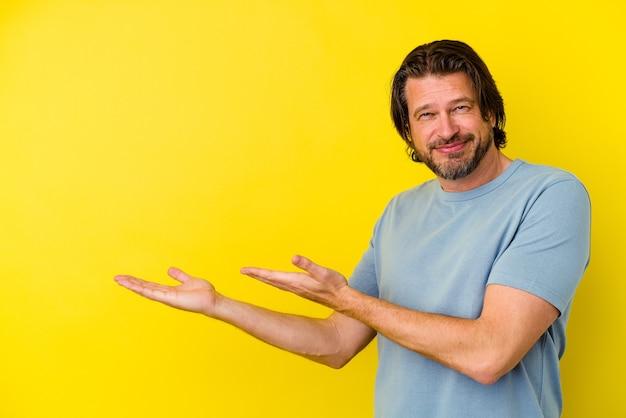 Kaukasischer mann mittleren alters isoliert auf gelbem hintergrund, der einen kopienraum auf einer handfläche hält.