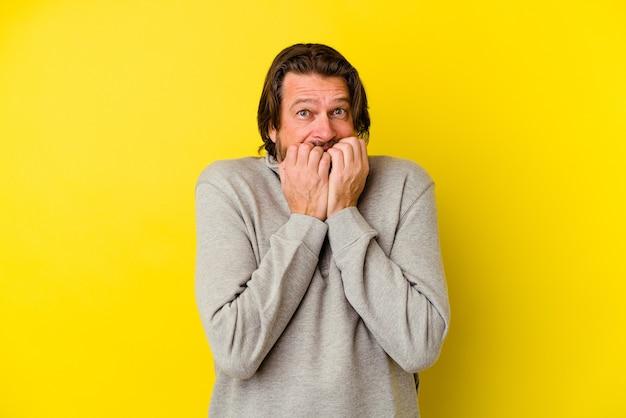 Kaukasischer mann mittleren alters isoliert auf gelber wand beißen fingernägel, nervös und sehr ängstlich.