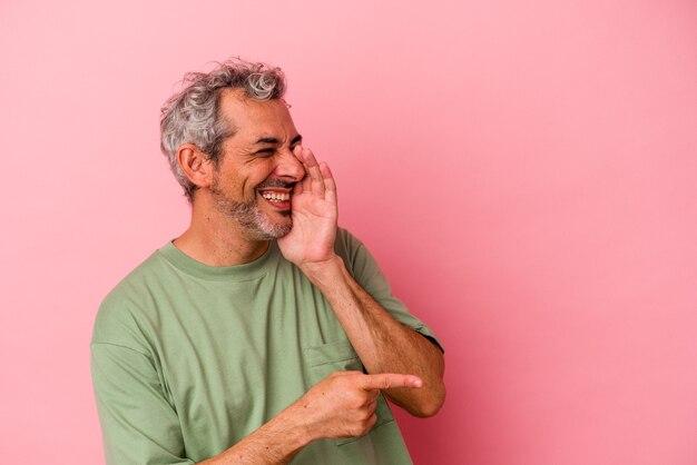Kaukasischer mann mittleren alters isoliert auf rosa hintergrund, der einen klatsch sagt und auf die seite zeigt, die etwas meldet.