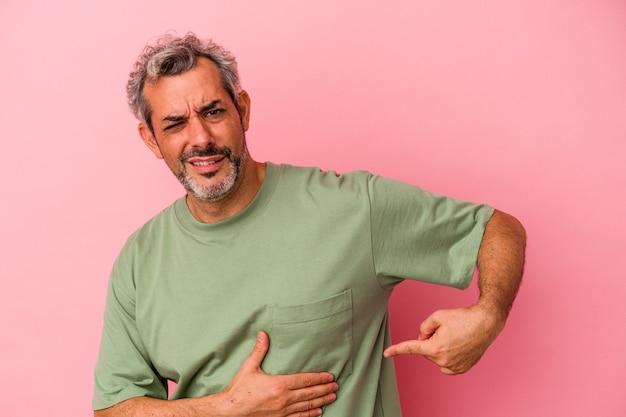 Kaukasischer mann mittleren alters isoliert auf rosa hintergrund mit leberschmerzen, bauchschmerzen.