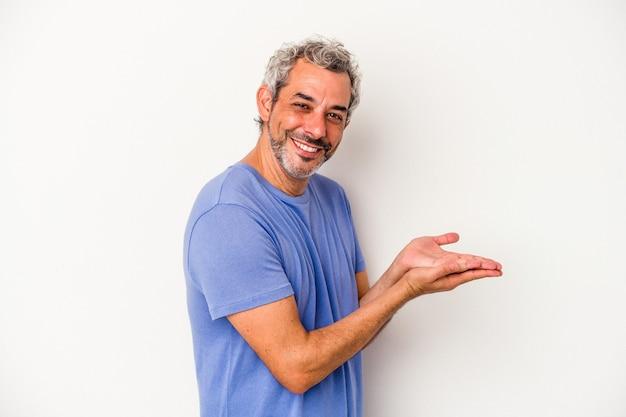 Kaukasischer mann mittleren alters isoliert auf weißem hintergrund, der einen kopienraum auf einer handfläche hält.