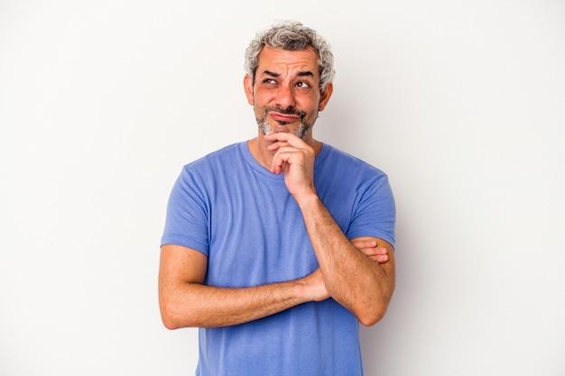 Kaukasischer mann mittleren alters isoliert auf weißem hintergrund, der seitlich mit zweifelhaftem und skeptischem ausdruck schaut.