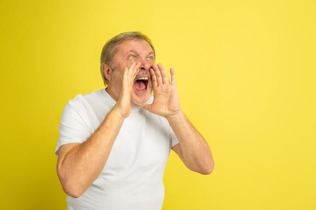 Kaukasischer mann ruft, schreiend isoliert auf gelb
