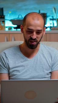 Kaukasischer mann sitzt auf der couch im pyjama und arbeitet an einem laptop