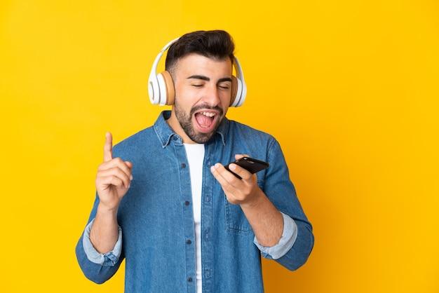 Kaukasischer mann über isolierter gelber wand, die musik mit einem handy hört und singt