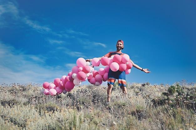 Kaukasischer mann, umgeben von einer reihe rosa luftballons, während er auf einem berg steht