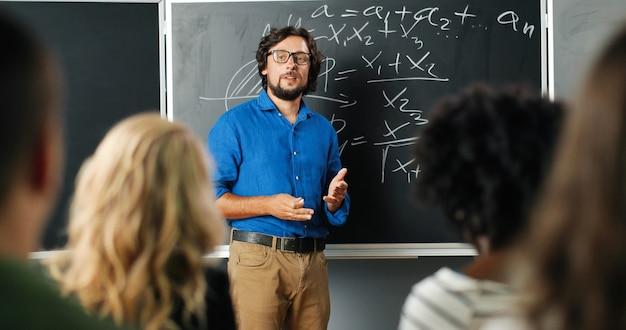Kaukasischer mannlehrer an der schule an der tafel, die mit schülern oder schülern spricht und frage stellt. matheklassenkonzept. männlicher dozent in gläsern, die kindern mathematikgesetze erklären. bildungskonzept