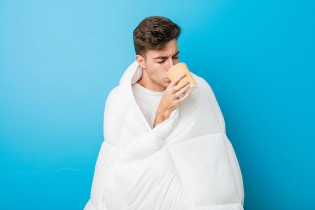 Kaukasischer müder mann des jugendlichen, der mit einer decke sich bedeckt und einen kaffee hält