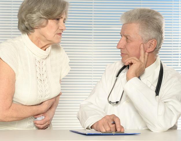 Kaukasischer netter alter arzt mit einem patienten auf hellem hintergrund