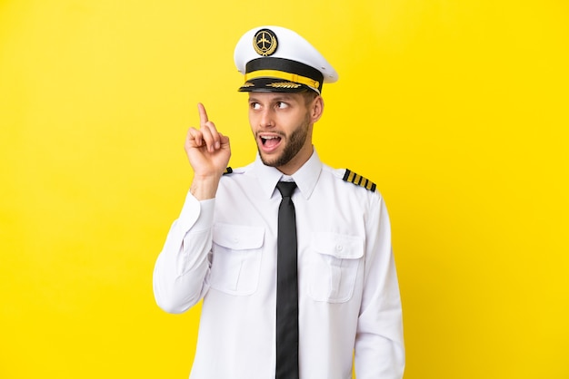 Kaukasischer pilot des flugzeugs, der auf gelbem hintergrund isoliert ist und beabsichtigt, die lösung zu realisieren, während er einen finger nach oben hebt