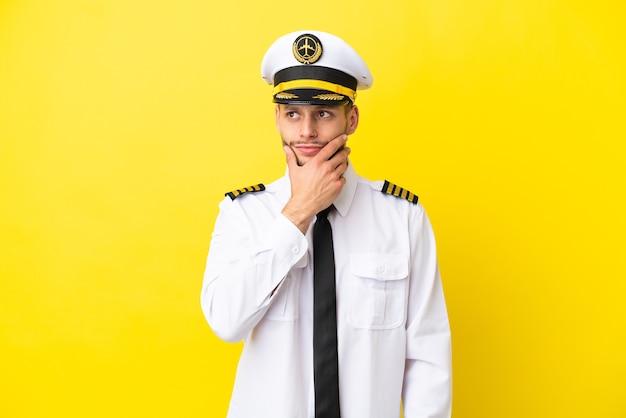 Kaukasischer pilot des flugzeugs einzeln auf gelbem hintergrund mit zweifeln und mit verwirrendem gesichtsausdruck