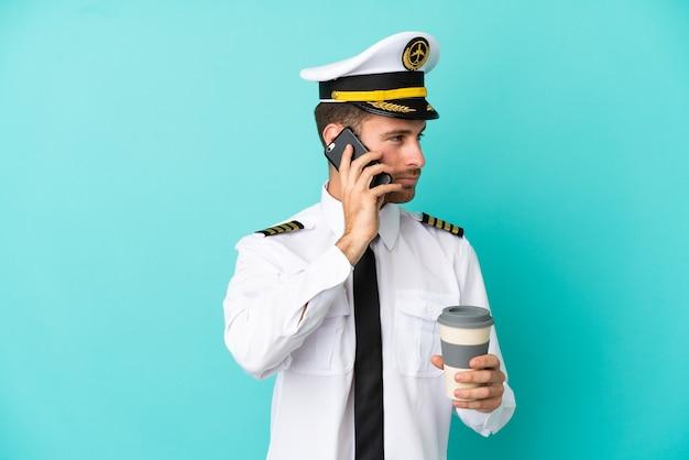 Kaukasischer pilot des flugzeugs lokalisiert auf blauem hintergrund, der kaffee zum mitnehmen und ein handy hält