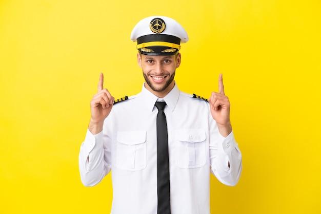 Kaukasischer pilot des flugzeugs lokalisiert auf gelbem hintergrund, der auf eine großartige idee zeigt