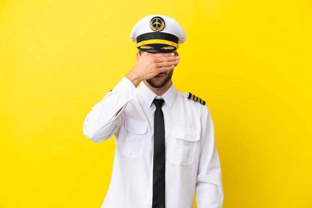 Kaukasischer pilot des flugzeugs lokalisiert auf gelbem hintergrund, der die augen mit den händen bedeckt. will etwas nicht sehen