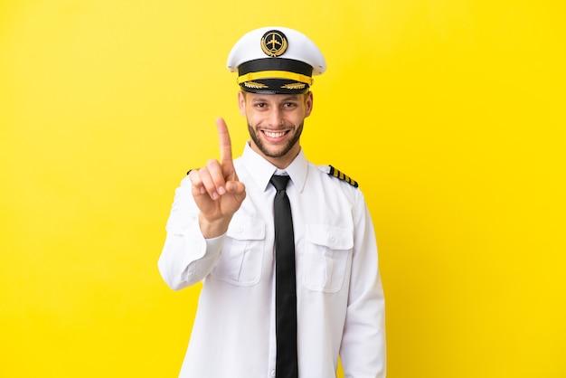 Kaukasischer pilot des flugzeugs lokalisiert auf gelbem hintergrund, der einen finger zeigt und anhebt