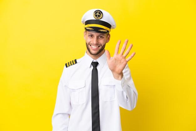 Kaukasischer pilot des flugzeugs lokalisiert auf gelbem hintergrund, der fünf mit den fingern zählt