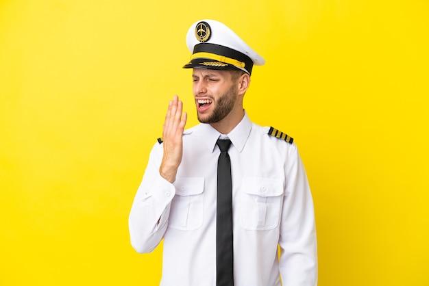 Kaukasischer pilot des flugzeugs lokalisiert auf gelbem hintergrund, der gähnt und weit geöffneten mund mit der hand bedeckt