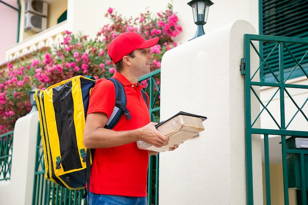 Kaukasischer postbote, der klemmbrett und paket vor haus hält. professioneller kurier in roter uniform mit gelbem thermorucksack, der bestellung liefert. hauslieferdienst und postkonzept