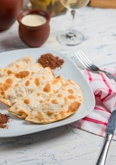 Kaukasischer qutab, kutab, gozleme, serviert mit sumakh, kräutern und joghurt.