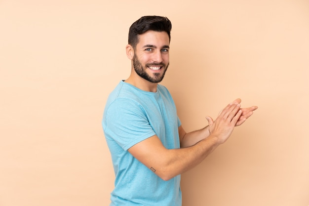 Kaukasischer schöner mann auf beige wand applaudierend