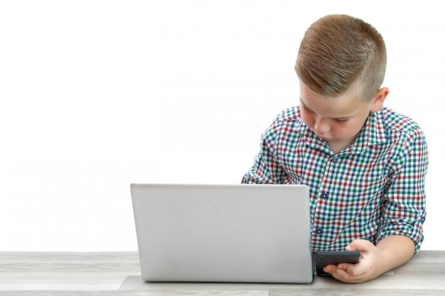 Kaukasischer schulpflichtiger junge in einem karierten hemd auf einem licht lokalisierte das spielen von spielen am telefon und gleichzeitig an. moderne kinder, ihre interessen