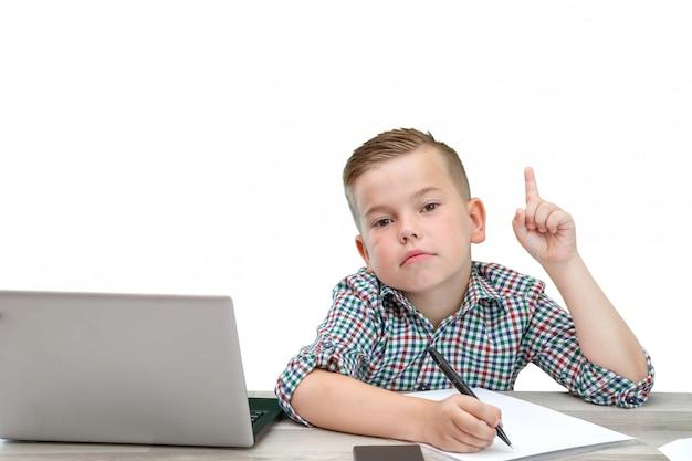 Kaukasischer schulpflichtiger junge in einem karierten hemd auf einem lokalisierten hintergrund mit einem laptop und einem telefon notiert gedanken in einem blatt papier.