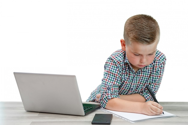Kaukasischer schulpflichtiger junge in einem karierten hemd, das am tisch sitzt und in ein blatt papier schreibt