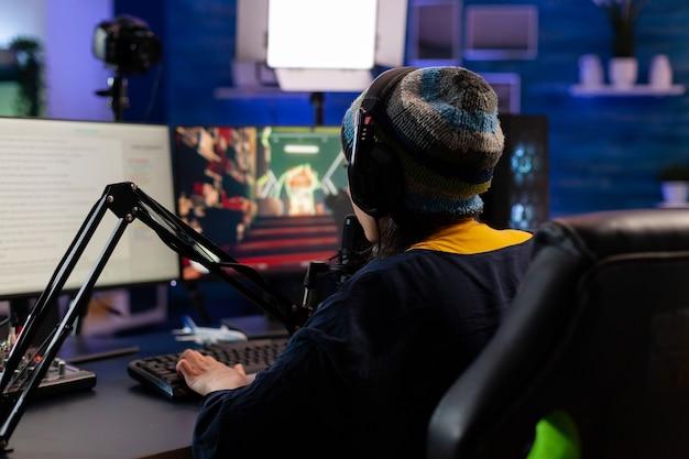 Kaukasischer spieler mit kopfhörern, der mit anderen spielern spricht, während er professionelle shooter-spiele im online-turnier spielt. spieler, die online-videospiele mit neuen grafiken auf einem leistungsstarken computer erstellen