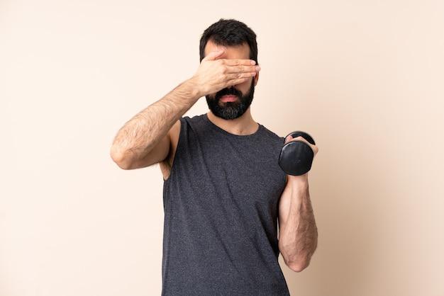 Kaukasischer sportmann mit bart, der gewichtheben, das augen durch hände bedeckt. ich will nichts sehen