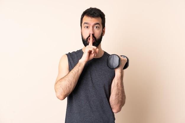 Kaukasischer sportmann mit bart, der gewichtheben über isolierter wand macht, die ein zeichen der stille geste zeigt finger in den mund setzt