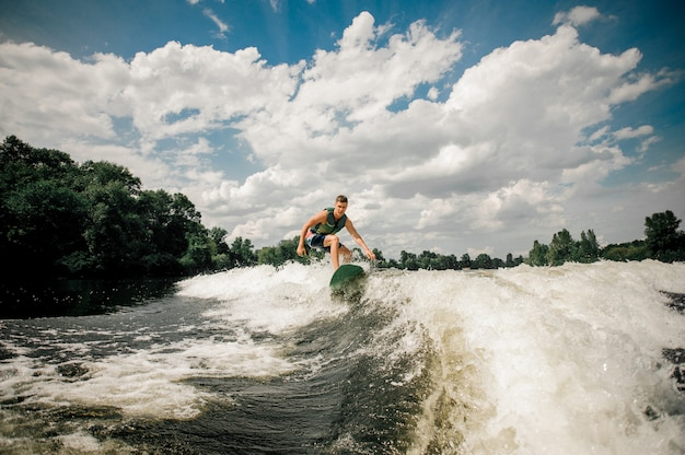 Kaukasischer surfer, der wakeboard auf der wasserlandschaft reitet