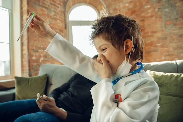 Kaukasischer teenager als arzt, der patienten zu hause berät, empfehlungen gibt, behandelt. kleiner arzt, der temperatur misst, schockiert, lacht. konzept der kindheit, menschliche emotionen, gesundheit, medizin.