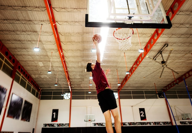 Kaukasischer teenager, der basketball allein auf dem gericht spielt