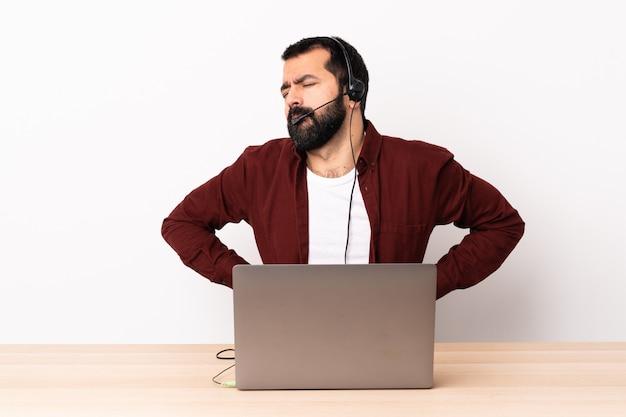 Kaukasischer telemarketer, der mit einem headset und mit einem laptop arbeitet, der unter rückenschmerzen leidet, weil er sich bemüht hat
