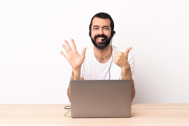 Kaukasischer telemarketer, der mit einem headset und mit laptop arbeitet, der sechs mit den fingern zählt.