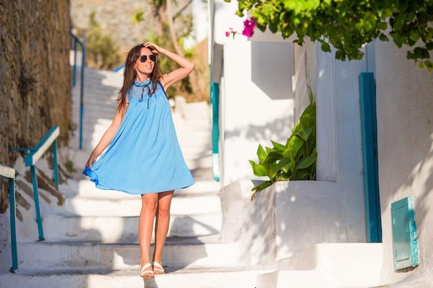 Kaukasischer tourist, der entlang die verlassenen straßen des griechischen dorfs geht. junge schönheit im urlaub, die europäische stadt erforscht