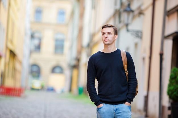 Kaukasischer tourist, der entlang die verlassenen straßen von europa geht. junger städtischer junge im urlaub, der europäische stadtkopfsteinstraße erforscht