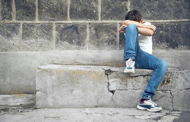 Kaukasischer trauriger junge, der in der straße sitzt.